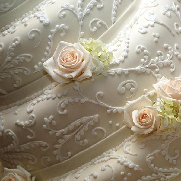 white wedding cake with white beading and roses